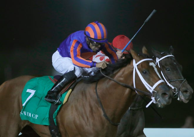 Jockey Luis Saez rides his horse, Maximum Security as he reaches the finish line of the $20 million, the Saudi Cup, at King Abdul Aziz race track in Riyadh, Saudi Arabia, Saturday. The race is considered the world's richest horse race which attracted some of the world's best jockeys.