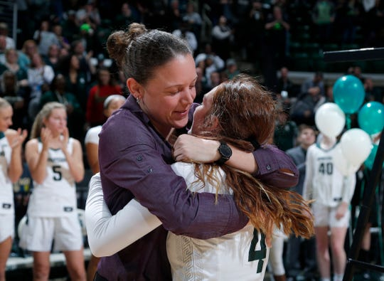 Michigan State's career assists leader Taryn McCutcheon, right, gets a hug from Kristin Haynie, who held the record previously, following a game against Penn State, Sunday, March 1, 2020, in East Lansing, Mich.
