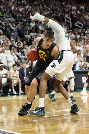 Luka Garza, left, leads the nation in scoring at 27.4 points per game.
