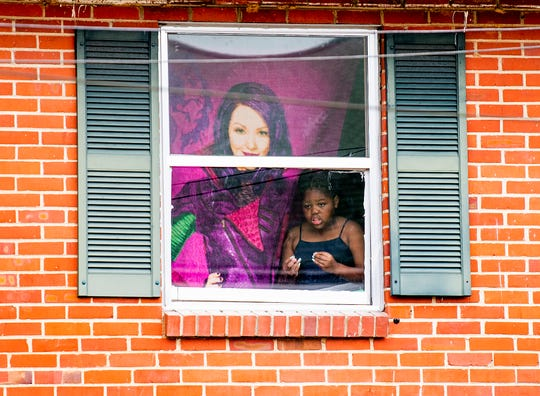 A child looks out her window in George Washington Carver housing as she watches the activities at Brown Chapel AME Church in Selma, Ala., on Sunday March 1, 2020. It is the 55th anniversary of the Selma Bloody Sunday Bridge Crossing.