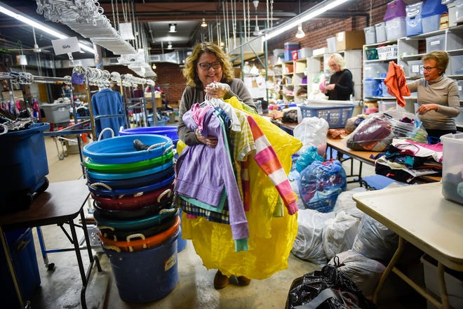 Karen Rowland divides clothing into categories as it is processed at Our Thrift Store in Franklin.