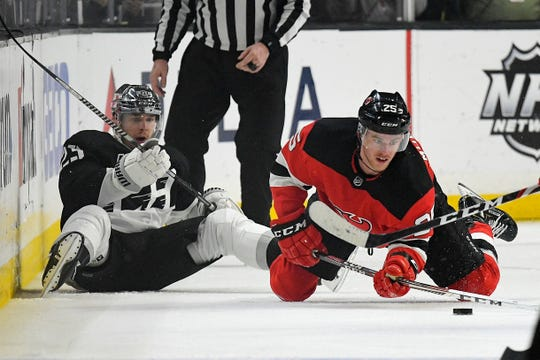 New Jersey Devils defenseman Mirco Mueller, right, passes the puck after falling along with Los Angeles Kings right wing Dustin Brown during the third period of an NHL hockey game Saturday, Feb. 29, 2020, in Los Angeles. The kings won 2-1 in overtime.