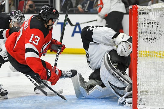 New Jersey Devils center Nico Hischier, left, is tripped up as Los Angeles Kings goaltender Jonathan Quick stops his shot during the third period of an NHL hockey game Saturday, Feb. 29, 2020, in Los Angeles. The kings won 2-1 in overtime.