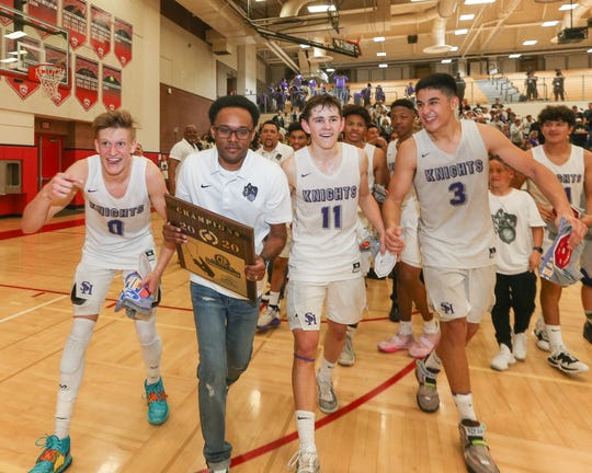 Shadow Hills' Cord Stansberry (0), head coach Ryan Towner, Cole Osgood (11) and Dominic Escobar (3) take the CIF-SS championship trophy over to the large Shadow Hills crowd after winning Saturday night.