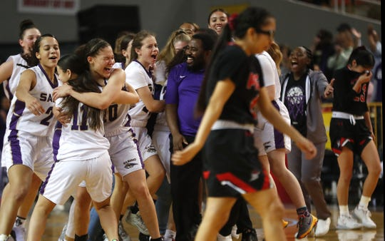 Sabino's Kiya Dorroh (24) and Kamryn Doty (10) rush the court with their teammates and coach after winning the 3A State Championship game against Page at Veterans Memorial Coliseum in Phoenix, Ariz. on Feb. 29, 2020.
