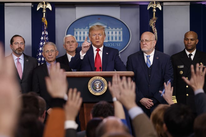 President Donald Trump, center, points as he prepares to answer question after speaking about the coronavirus in the press briefing room at the White House, Saturday, Feb. 29, 2020, in Washington, as Health and Human Services Secretary Alex Azar, National Institute for Allergy and Infectious Diseases Director Dr. Anthony Fauci, Vice President Mike Pence, Robert Redfield, director of the Centers for Disease Control and Prevention and U.S. Surgeon General Dr. Jerome Adams listen. (AP Photo/Carolyn Kaster)