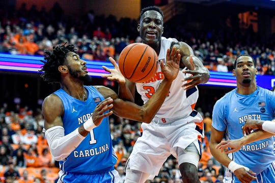 North Carolina guard Leaky Black, left, and Syracuse forward Bourama Sidibe reach for a rebound during the second half of an NCAA college basketball game in Syracuse, N.Y., Saturday, Feb. 29, 2020. North Carolina defeated Syracuse 92-79. (AP Photo/Adrian Kraus)