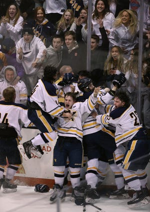 Victor celebrates its overtime goal by Cal Lambert to beat Fairport and win the Class A championship 5-4.