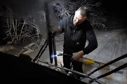 Dave Kowell uses a torch to melt ice off the windshield wipers on a snowmobile trail groomer on Friday, Feb. 28, 2020. Kowell, 35, volunteers his time to groom the trails and drives up to Osceola from his home in Syracuse three times a week to do it in the winter.