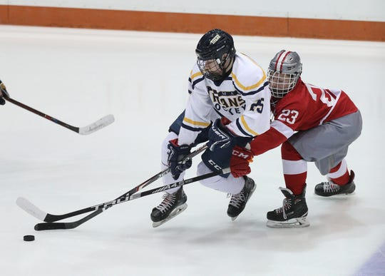 Cade Spencer of Webster Thomas carries the puck ahead of Canandaigua's Anthony Holtz during the Section V Class B championship game.