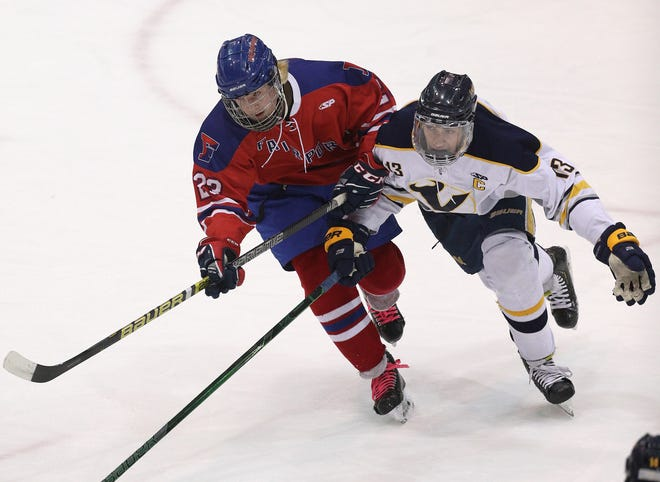 Fairport's Colin Herington (23) and Victor's Jack McCandless chase a loose puck.