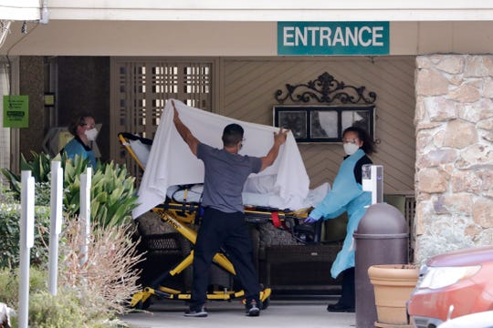 A person is taken by stretcher to a waiting ambulance from a nursing facility where more than 50 people are sick and being tested for the COVID-19 virus, Saturday, Feb. 29, 2020, in Kirkland, Wash.