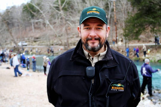 Joel Topham stands on the banks of the river where he would fish as a boy with his grandparents. Now, he is the manager at Roaring River State Park.