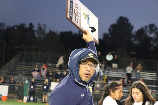 Santa Clara head coach Jose Albert Pina accepts the CIF-Southern Section Division 7 runner-up plaque on Saturday night in Temecula. The Saints fell to host Linfield Christian in the final, 3-2, in overtime.