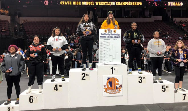 Newbury Park High's Julia Richey stands with the bracket and on the first-place spot after winning the 235-pound girls title at the state wrestling championships in Bakersfield on Saturday.