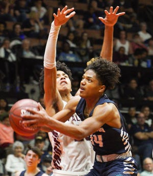 Redwood High's Malachi Aguilar drives to the basket for two points during the Central Section Division II championship boys basketball game between Redwood and Independence.