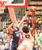 Redwood High's Conner Gilcrest  blocks the shot of Independence High's Zarek Williams during the Central Section Division II championship boys basketball game between Redwood and Independence.