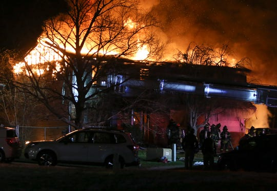 Firefighters battle a blaze that hospitalized several people and gutted a house on Barrister Court near New Castle late Saturday night. The fire, reported about 11:45 p.m., was engulfing the house when firefighters arrived and caused a partial collapse of the home.