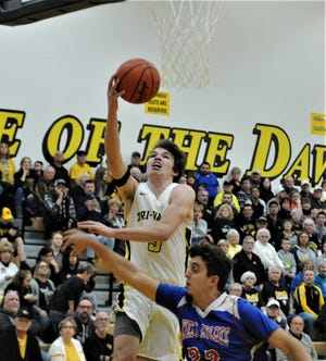 Tri-Valley's Keaton Williams goes up for a layup over West Holmes' Garrett Eastep in Saturday's 66-43 win in the Division II sectional final on Saturday.