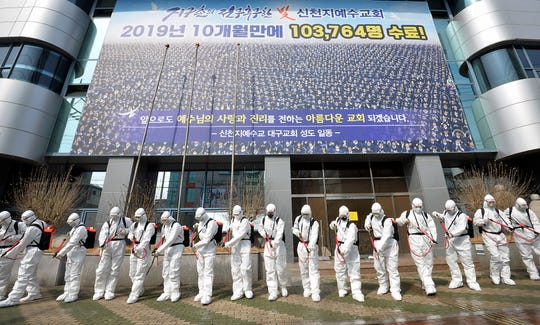 Army soldiers wearing protective suits spray disinfectant to prevent the spread of the coronavirus in front of a branch of the Shincheonji Church of Jesus in Daegu, South Korea, Sunday, March 1, 2020. The coronavirus has claimed its first victim in the United States as the number of cases shot up in Iran, Italy and South Korea and the spreading outbreak shook the global economy.