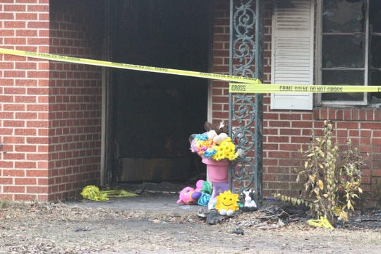 People left flowers and stuffed animals at the Alexandria home where a grandmother, Verlana Cooper, and her three granddaughters died in a fire late Saturday.