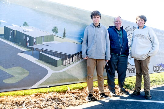 Dominique, Nick and Matteo Williams stand next to a rendering of the Noakes Center at the French Broad River Academy February 27, 2020.