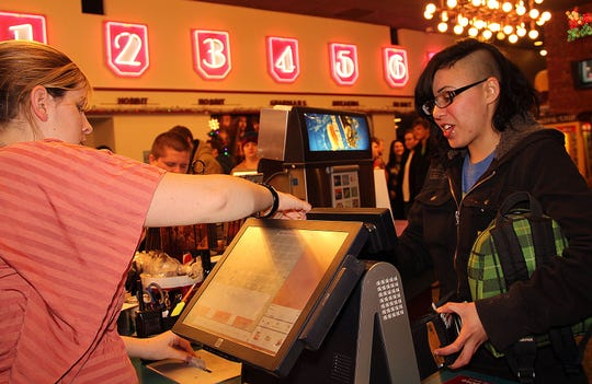 """In this 2012 file photo, Adelle Pouliot purchases a ticket from shift manager Meagan Metheny for the midnight premiere of """"The Hobbit"""" at West Columbia 7 in Battle Creek."""