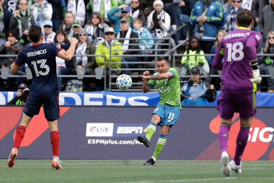 Seattle Sounders defender Miguel Ibarra (11) takes a shot as Chicago Fire midfielder Brandt Bronico, left, and goalkeeper Kenneth Kronholm, right, defend, during the first half of an MLS soccer match, Sunday, March 1, 2020, in Seattle. (AP Photo/Ted S. Warren)