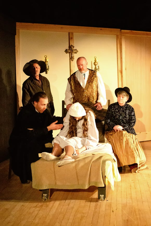 """Reverend Hale (Kristopher Jones, lower left) tries to reason with the possessed Betty Paris (Ava Emory) in Western Washington Center for the Arts' """"The Crucible."""""""