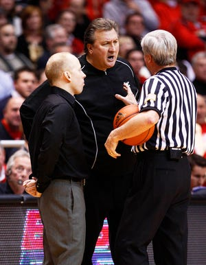 Cincinnati Bearcats head coach Mick Cronin (l) and West Virginia Mountaineers head coach Bob Huggins (c) talk to the referee in the first half at the Fifth Third Arena in January 2011.