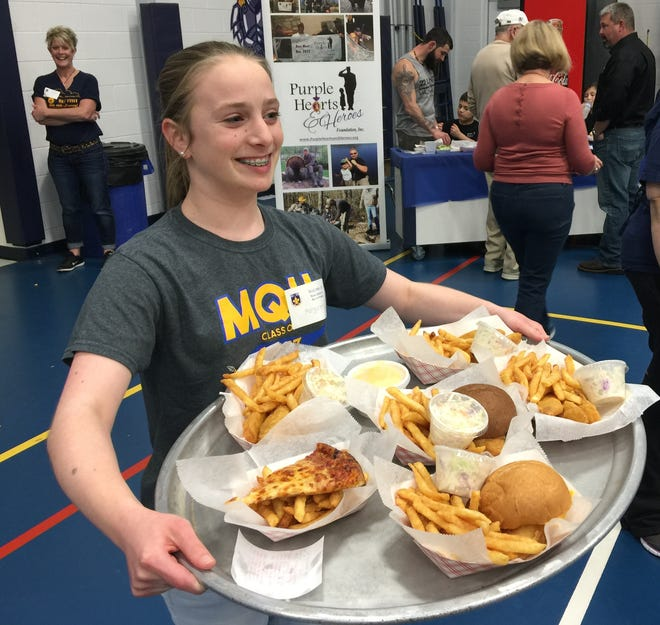 Margaret Gardner, of Erlanger, brings out a tray of dinners to serve at the Mary, Queen of Heaven Fish Fry in 2017.
