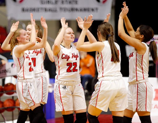 Iowa City High players celebrate after beating Cedar Rapids Prairie during the quarterfinal round Monday at the Iowa girls' basketball state tournament.