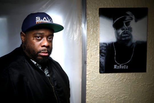Kamal Lukata Anderson of Detroit next to a portrait his mother painted of him three years ago that hangs in the dining room of his home on February 27, 2020. Anderson is one of many that have had to deal with suspended driver's license and court costs. He had his license suspended back in 1994 and it took him years to get things back on the right track.