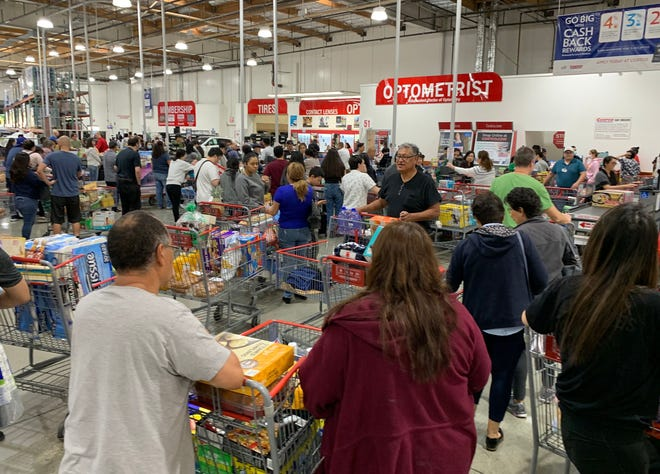 Shoppers buy toilet paper, food and water at a store in Los Angeles, California, on Saturday, as people begin to panic buy and stockpile essentials from fear that supplies will be affected by the spread of the COVID-19, coronavirus outbreak across the country.