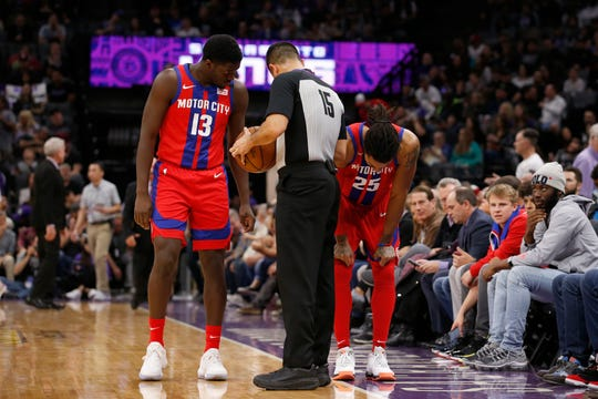 Pistons guard Khyri Thomas, left, and referee Zach Zarba check on Pistons guard Derrick Rose after he sustained an injury during the first half against the Kings in Sacramento, Calif., March 1, 2020