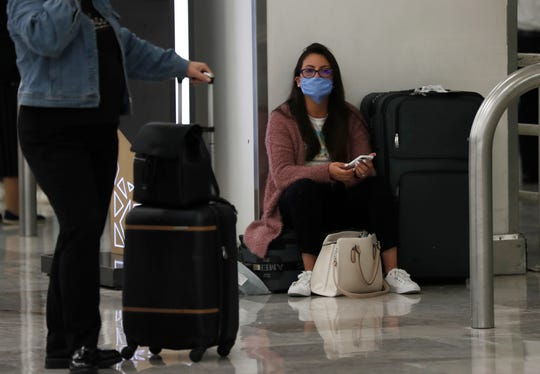 A woman wears a protective masks as a precaution against the spread of the new coronavirus at the airport in Mexico City, Friday, Feb. 28, 2020. Mexico assistant health secretary announced Friday that the country now has confirmed cases of the COVID-19 virus.