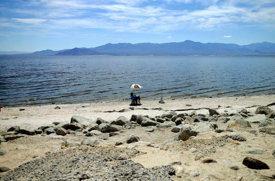 A man fishes along the receding banks of the Salton Sea near Bombay Beach, Calif.
