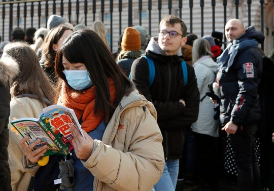 A tourist wears a face mask as people watch the Changing of the Guard, at Buckingham Palace, in London, Monday, March 2, 2020.