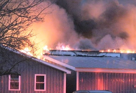 Flames are visible along the roof of Austin Construction in the Town of Campbell.