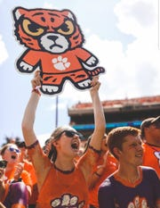 A University of Clemson student cheers on her football team with a Tokyodachi cutout.