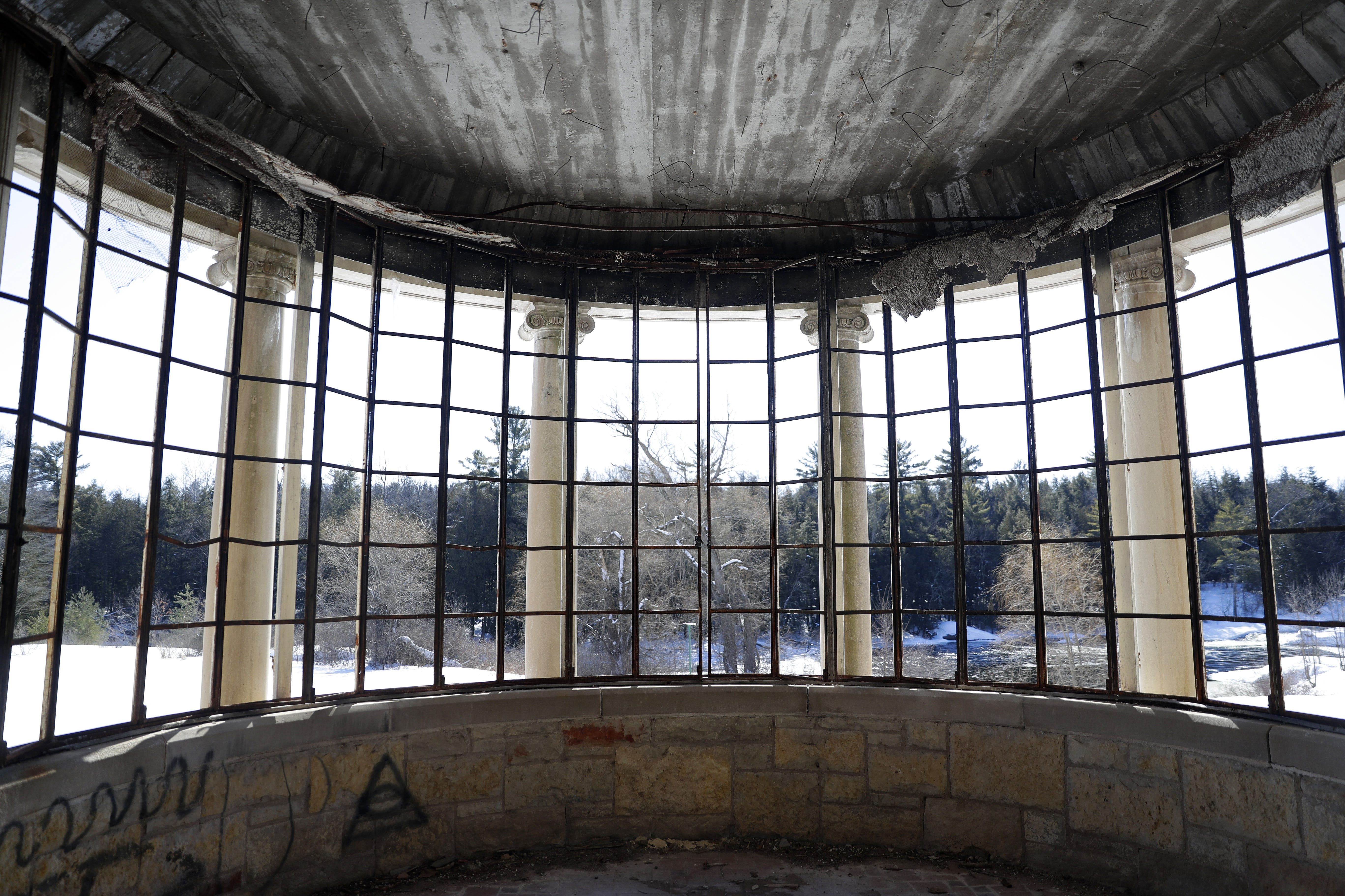 Windows without any glass in the former conservatory room of a 25,000-square-foot limestone mansion overlook the former grounds of the former Alexian Brothers Novitiate in Gresham.