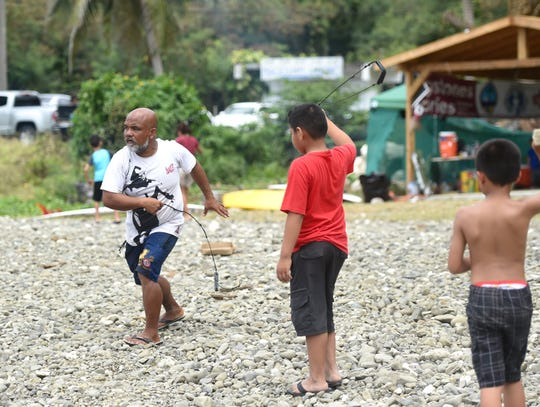 Roman Dela Cruz shows kids how to sling at the Guam History and Heritage Festival in Umatac, March 2, 2020.