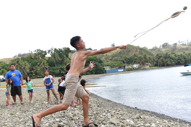 Xavier Santos demonstrates slinging stones into Umatac Bay at the Guam History and Heritage Festival in Umatac, March 2, 2020.