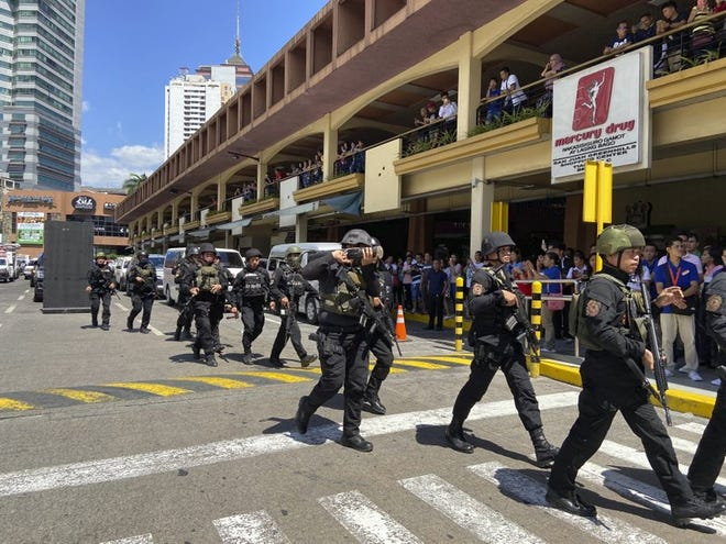 A group of armed police arrive at the Greenhills Shopping Center Monday, March 2, in Manila. Philippine police on Monday surrounded a shopping mall in an upscale district in the Manila metropolis after gunshots rang out inside and sent shoppers rushing out in panic.