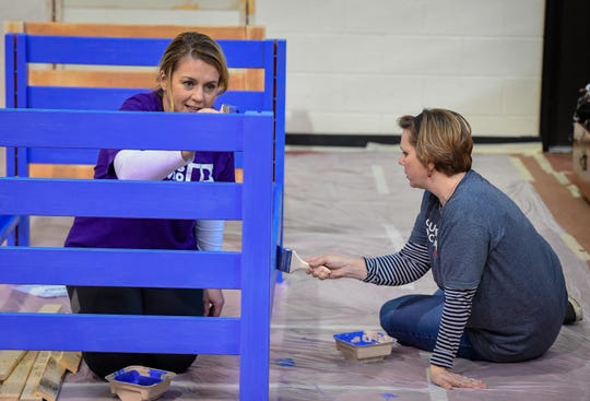Missy Vanderpool, left, and Lori Stevens put the finishing touches on a bed frame paint job Saturday morning during the Volunteer and Information Center's 2020 Build-A- Bed Project.