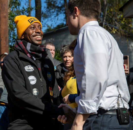 Jermaine Archie, a volunteer from Los Angeles, meets Pete Buttigieg during a small backyard appearance by the presidential candidate for a group of about forty volunteers and canvassers on the day of the democratic primary in South Carolina, Columbia, Saturday, Feb. 29, 2020. Archie said he's looking forward to talking with people in California about Buttigieg.