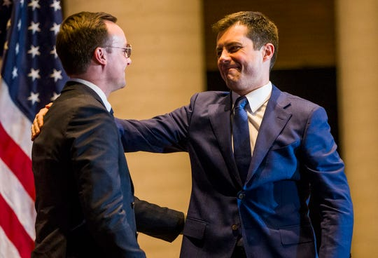 Former South Bend Mayor Pete Buttigieg, right, hugs his husband, Chasten Buttigieg, before ending his presidential campaign during a speech to supporters, Sunday, March 1, 2020, in South Bend, Ind. (Michael Caterina/South Bend Tribune via AP)