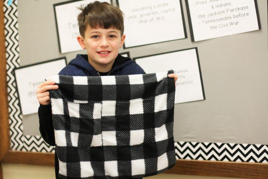 """Miles Bruner shows his """"Cozy Keeper"""" prototype at the Adrian Burnett Elementary School Invention Convention on Feb. 27."""