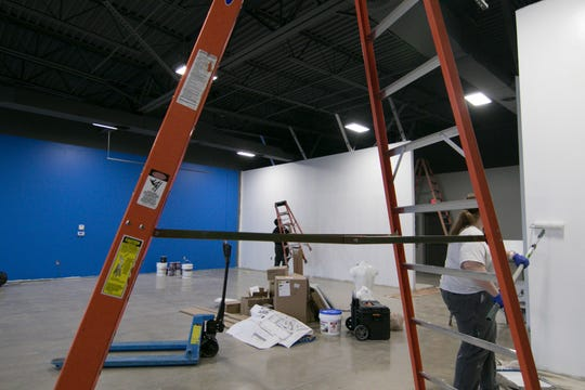 Painters make ready the new location for D & D Bicycles Monday, March 2, 2020, across the street from its former location in Brighton Township.