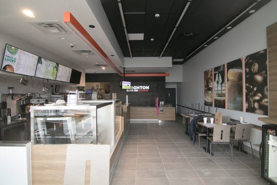 A view through the window of one of the storefronts in Brighton Gate Commons Monday, March 2, 2020, shows the Dunkin' Donuts business preparing to open.